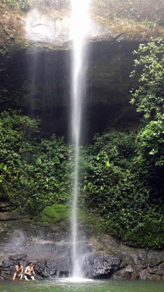 Fotografía de la cascada de la Sierpe cayendo en la piscina natural y unos turistas al lado