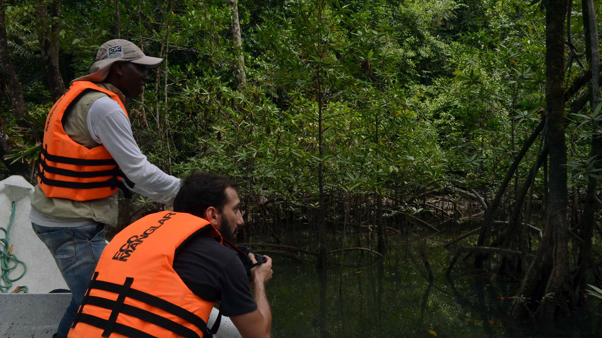 Fotografía de un guía y un turista con cámara fotográfica recorrido por los manglares en lancha