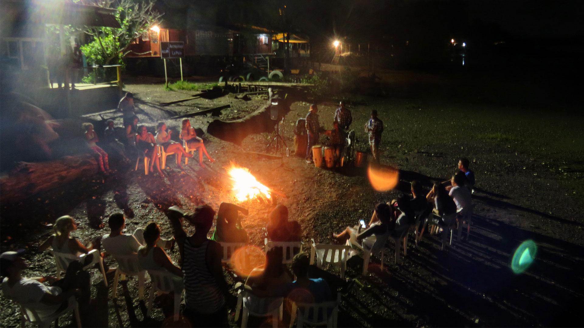 Fotografía de una fiesta nocturna con fogata y música folclórica