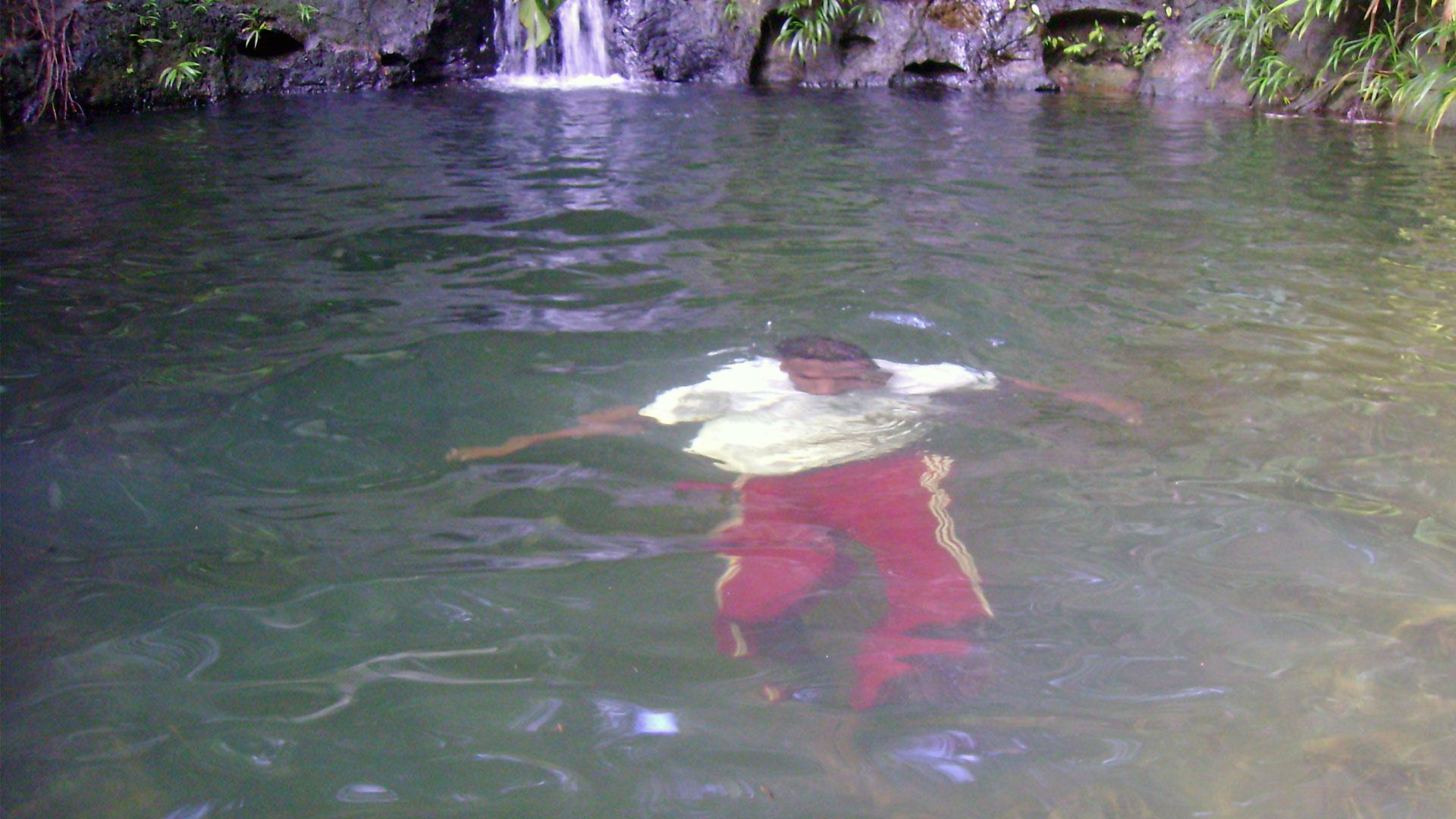 Fotografía de una persona sumergida dentro de la piscina natural